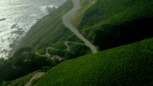 A car travels on a road at California's Big Sur along the cliffs over the Pacific coast.