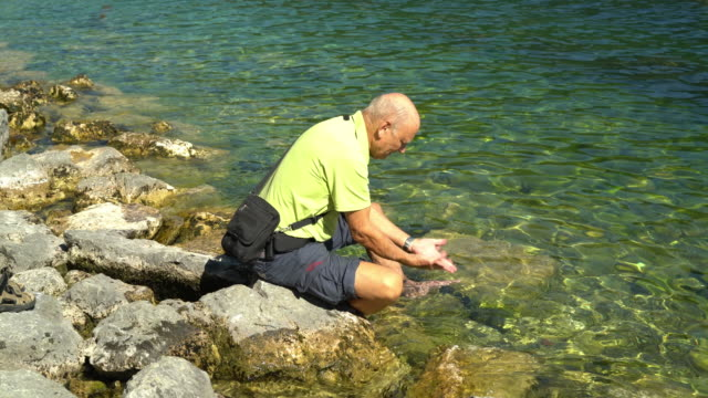 Car Trip, active senior man refreshing in lake and washing hands
