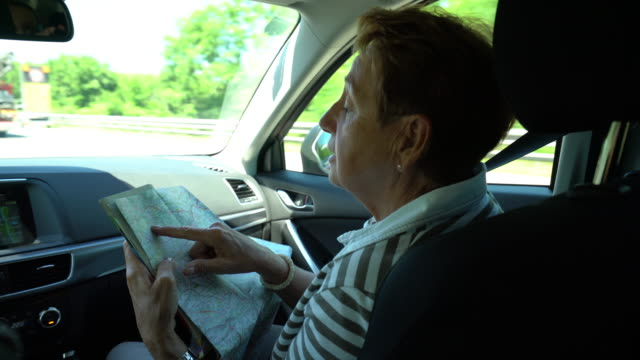 car trip, happy senior woman in car with road map - direction stock videos & royalty-free footage