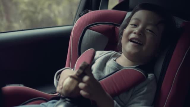 vídeos de stock, filmes e b-roll de viagem de carro - cadeirinha cadeira