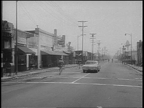 B/W 1965 car troops running on city street after Watts race riots Los Angeles / newsreel