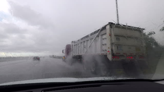 tropical downpours near miami fl create treacherous driving conditions for motorists on i95 a dump truck sprays water in every direction due to water... - hialeah stock videos & royalty-free footage