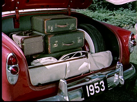 1952 CU Car trunk filled with luggage / Man closing car trunk / 1953 license plate / USA
