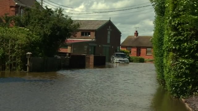 a car trying to navigate down a flooded street in wainfleet lincolnshire - land stock videos & royalty-free footage