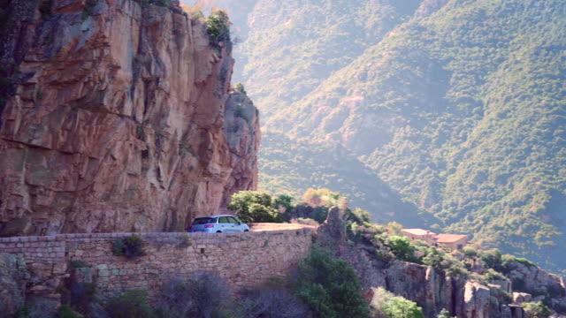 car turning on a windy mountain road, pan right ms - カランシェ点の映像素材/bロール