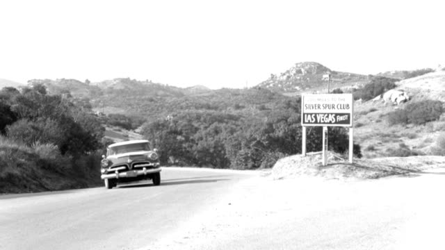 """a car turns a corner past a road sign that reads """"200 miles to the silver spur las vegas finest."""" - 1958 stock videos & royalty-free footage"""