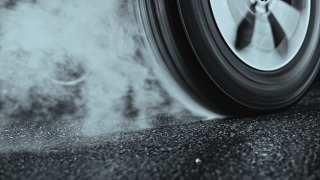 car tyre rotating in place and smoking - tyre stock videos & royalty-free footage