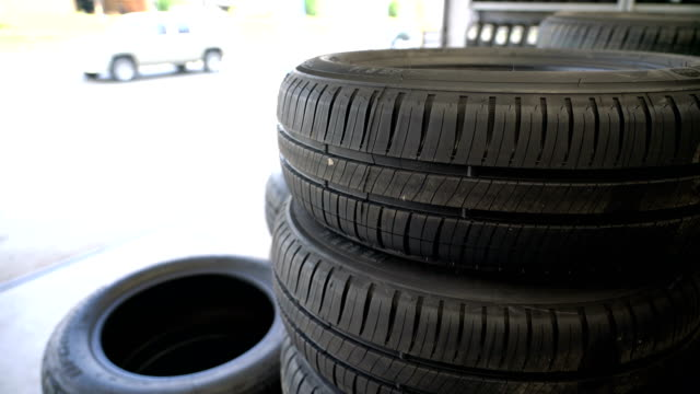 car tyres stack in garage. - rastrelliera video stock e b–roll