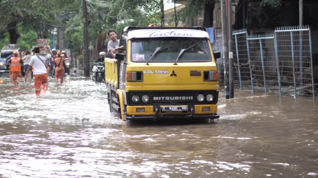 car wades through flooded road in jakarta, indonesia 25 februari 2020 heavy rains triggered widespread flood in jakarta inundating thousand homes. - jakarta stock videos & royalty-free footage