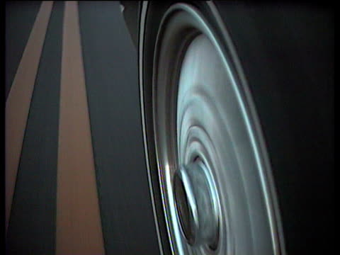 Car wheel spinning around as car drives along road past yellow road markings