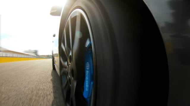 car wheel spinning at a race track, passing the start/finish line - tire vehicle part stock videos and b-roll footage