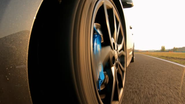 car wheel spinning, driving on an empty road - tyre stock videos & royalty-free footage