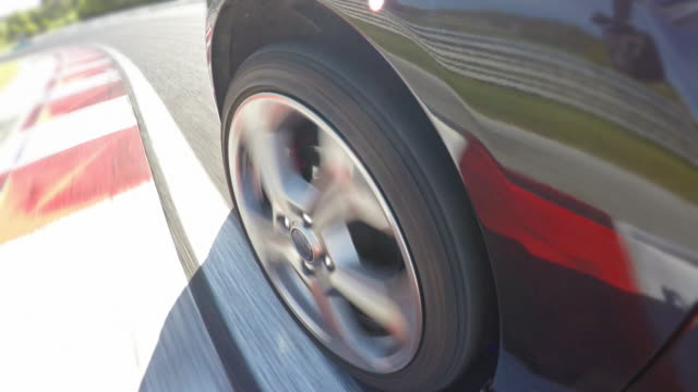 Car wheel spinning while driving fast at a race track, finishing a lap