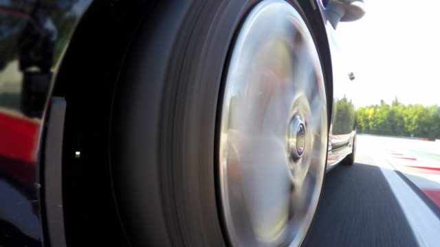 Car wheel spinning while driving fast at a race track, training for competition round