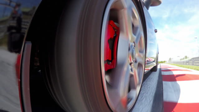 car wheel spinning while driving fast at a race track, training for competition round - wheel stock videos & royalty-free footage