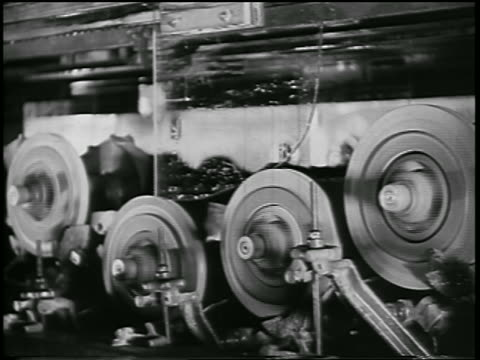 b/w 1932 car windows on conveyor getting smoothed by grindstones in ford car factory / industrial - 研ぐ点の映像素材/bロール