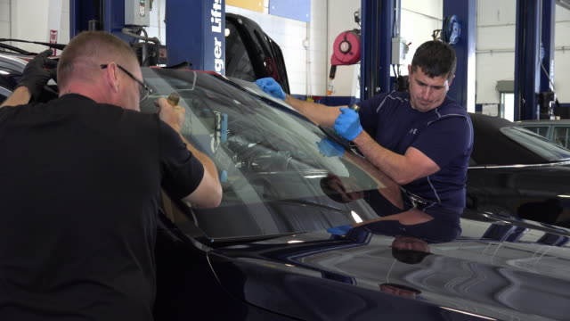 car windshield is installed by two workers at a garage in chattanooga, tn. no audio - personal land vehicle stock videos & royalty-free footage