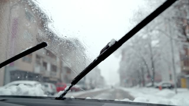 Car windshield wipers clearing snow and slush, driving on winter road, super slow motion