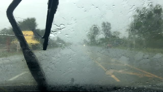 Car wipers are removing rain at slow and drive on road