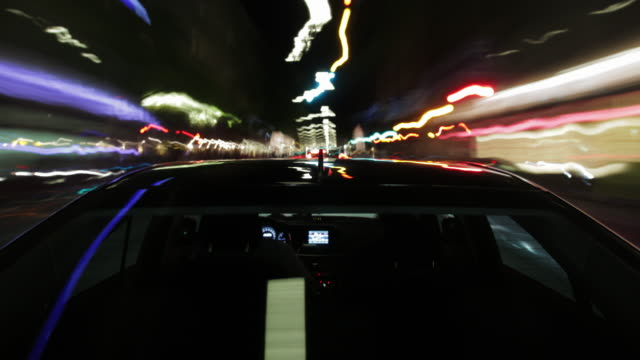 MS T/L POV Car with antenna in middle ground driving through city during night / Munich, Bavaria, Germany