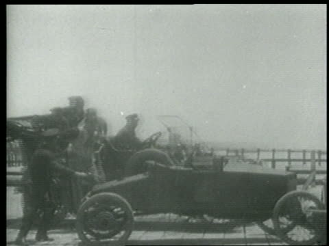 stockvideo's en b-roll-footage met b/w 1915 car with keystone kops stopping / people getting out + pointing to something offscreen - 1915