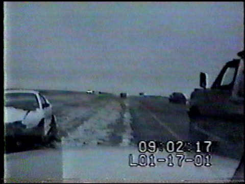 / car wreck on side of road man waiting for tow truck help / flat bed truck pulling into area / car sliding on ice crashes into flat bed tow truck... - 衝突事故点の映像素材/bロール