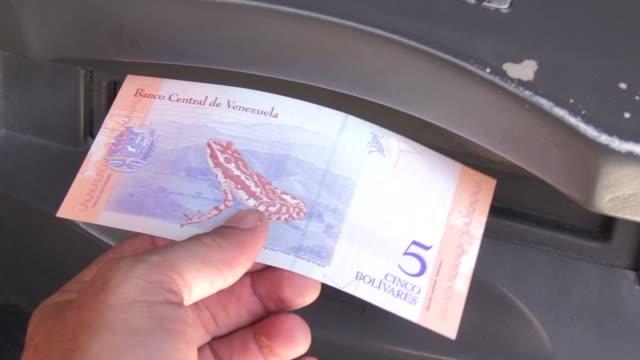 vídeos y material grabado en eventos de stock de caracas axes fives zeroes off the bolivar and issues new banknotes as part of president nicolas maduro's radical new plan to curb the spiralling... - accesorio financiero