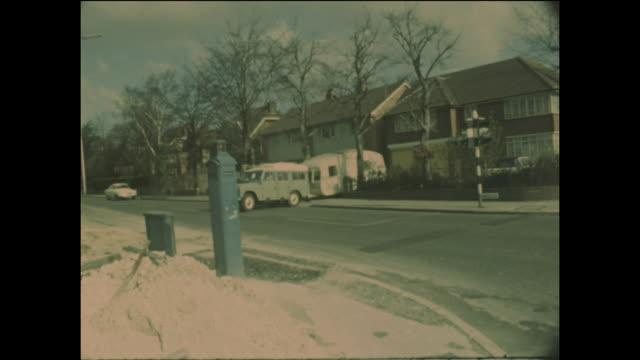 stockvideo's en b-roll-footage met caravan being towed behind a four wheel drive vehicle leaving a suburban house in england circa 1970 - aanhangwagen