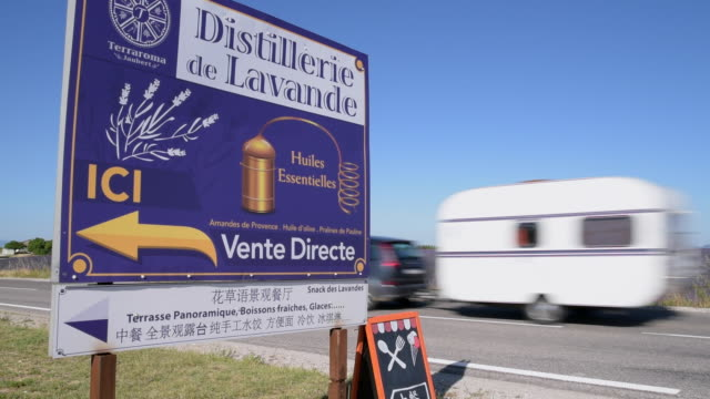 a caravan drive past a lavender distillery sign - camper trailer stock videos and b-roll footage