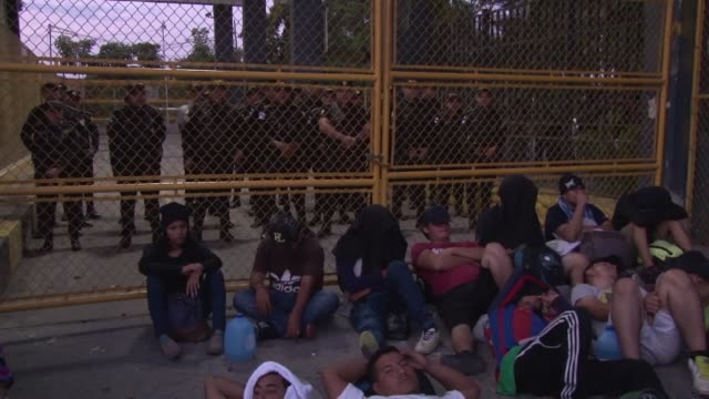 vídeos de stock e filmes b-roll de a caravan of about 1000 salvadoran migrants rests at a border gate between guatemala and mexico waiting for authorities to let them through in hopes... - escolta