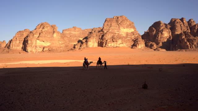 晴れた日にヨルダンのワディラム砂漠を歩くラクダのキャラバン - ラクダ点の映像素材/bロール