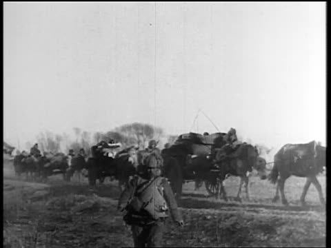 caravan of horse-drawn carts moving across field with troops / japan invading manchuria - manchuria stock videos & royalty-free footage