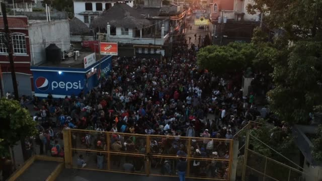 a caravan of migrants from el salvador waits at the border gate separating guatemala from mexico in hopes of continuing its journey toward the united... - convoglio video stock e b–roll