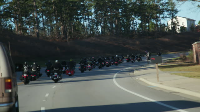 Caravan of motorcycle club members drive on highway