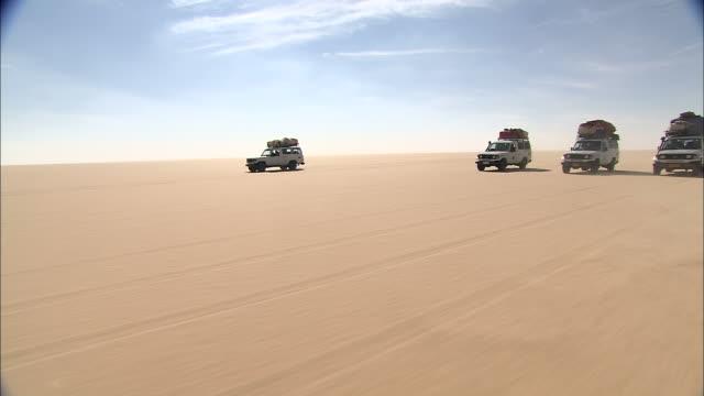 a caravan of suvs drive across the gilf kebir. - konvoi stock-videos und b-roll-filmmaterial