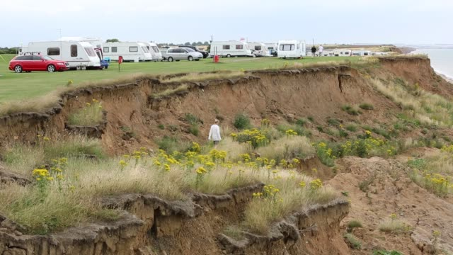 a caravan park near the edge of collapsing coastal cliffs at aldbrough on yorkshires east coast, uk. the coast is composed of soft boulder clays, very vulnerable to coastal erosion. this sectiion of coast has been eroding since roman times, with many vill - at the edge of stock videos & royalty-free footage