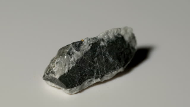 carbonaceous limestone mineral sample in rotation with white background - limestone stock videos & royalty-free footage