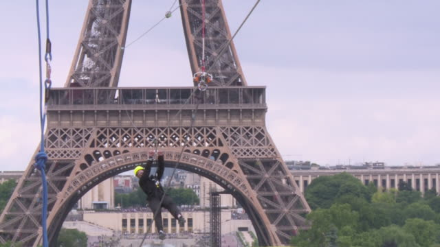 carbonated water producer perrier once again set up its zip line between the eiffel tower and the camps de mars in paris in 2019. adrenaline junkies... - 高揚点の映像素材/bロール