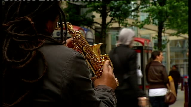 id card scheme launched in manchester ext people sitting outside cafe busker playing saxophone on street and shoppers along - woodwind instrument stock videos and b-roll footage