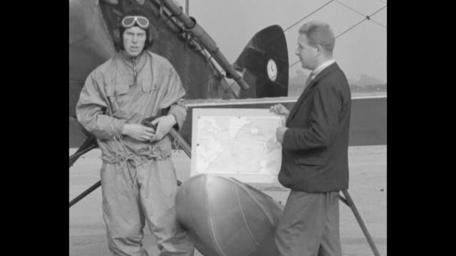 Card with intro info / Pilot John Grierson standing in front of seaplane at dock with another man holding map talks to camera about purpose of flight...
