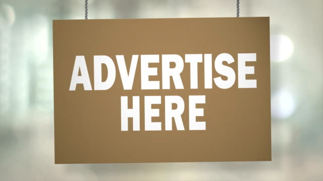 cardboard advertise here sign hanging from ropes. luma matte included so you can put your own background. - classified ad stock videos and b-roll footage