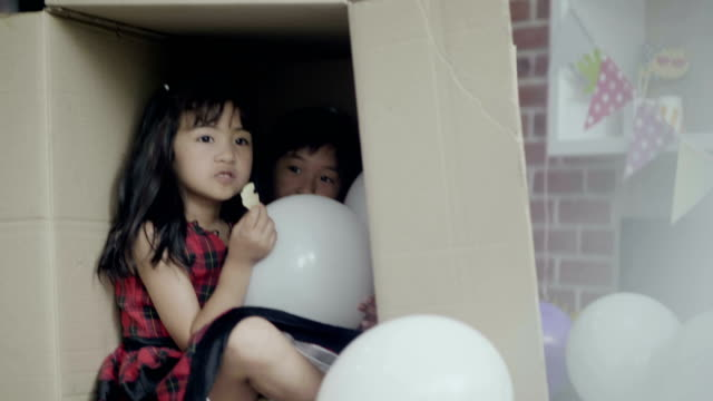 Cardboard Box : A little girl playing and eating snack