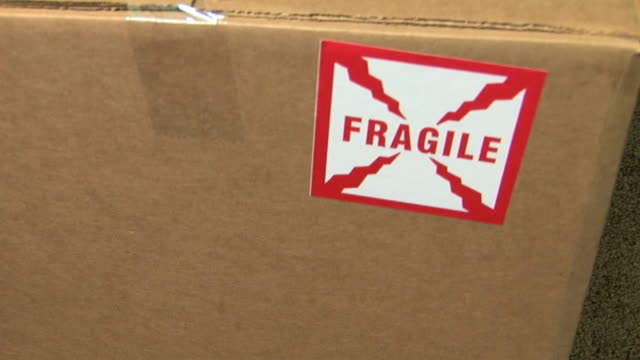 CU Cardboard box with 'fragile' sticker being dropped