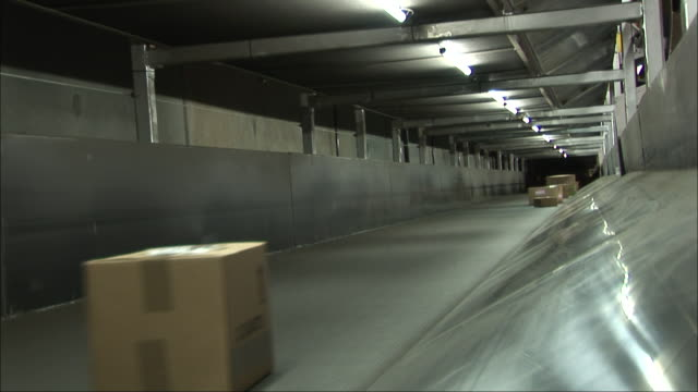 cardboard boxes move by on a conveyor system of a distribution center. - automated stock videos & royalty-free footage