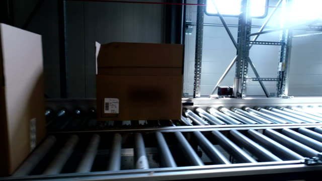cardboard boxes moving on a conveyor belt. close up - group of objects stock videos & royalty-free footage
