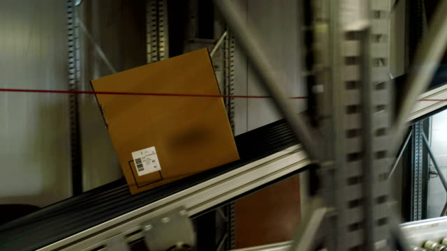 cardboard boxes moving on a conveyor belt. close up - e commerce stock videos & royalty-free footage