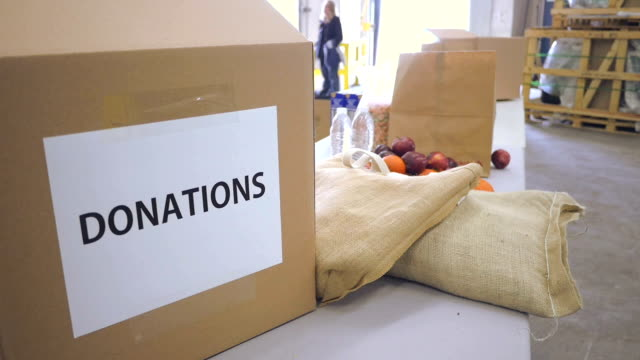 Cardboard donation boxes in food bank being filled with groceries
