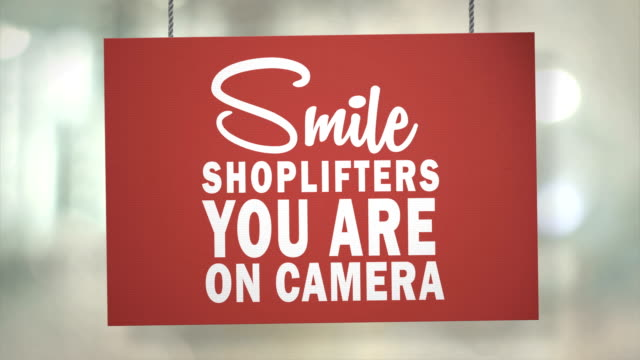 cardboard smile shoplifters you are on camera sign hanging from ropes. luma matte included so you can put your own background. - thief stock videos & royalty-free footage