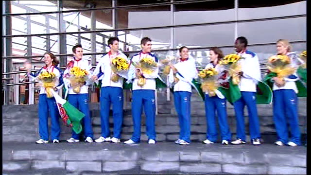 back view nicole cooke holding up welsh flag to cheering crowd cooke, geraint thomas , tom james , david davies and others posing with flowers pull... - typisch walisisch stock-videos und b-roll-filmmaterial