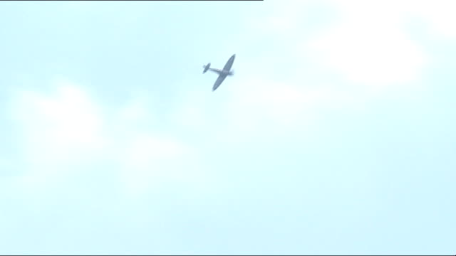 Cardiff Spitfire fighter plane fly over Soldiers marching along